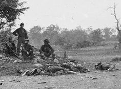 Union soldiers sitting with Confederate dead before them. Antietam.