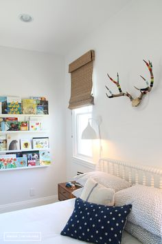 Lovely boy's room features faux antlers over white Jenny Lind Bed flanked by small mid-century modern nightstands illuminated by white sconces with wood folding stools placed at the foot of the bed atop West Elm Jute Chenille Herringbone Rug alongside walls lined with stacked book ledges, Ikea Ribba Picture Ledges.