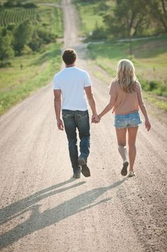 Holding hands, walking away.  Country road.