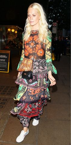 Poppy Delevingne wears a colorful, printed tiered long sleeve dress with tennis shoes and a crossbody bag.