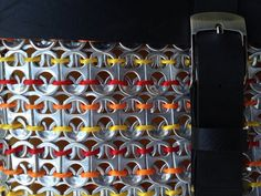 Aluminum tabs are collected from soda machines in schools and universities and recycled into this beautiful purse. This bag is 10 wide and