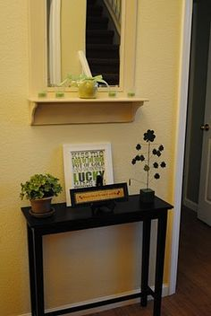 "small, skinny ""landing"" table in entryway?  mirror with shelf in entryway, maybe key hooks on the shelf and an old style coat tree next to it."