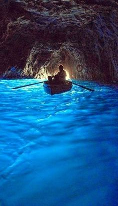 The Blue Grotto, Capri Italy. The sunlight shines in a cave with a small opening, reflects off the white sand then up through the water.