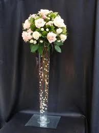 Battery powered fairy lights to fill the vase with pearls in the base. Cylinder Vase Centerpieces, Lighted Centerpieces, Tall Glass Vases, Quinceanera Centerpieces, Tall Wedding Centerpieces, Floral Centerpieces, Wedding Reception Table Decorations, Wedding Ideas, Wedding Inspiration