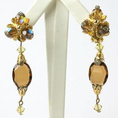 These classy Hattie Carnegie 1950s dangling earrings feature brown topaz and citrine rhinestones.