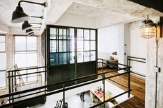 Warehouse converted to modern loft. Industrial lighting. Concrete. Black steel. Catwalk. Mezzanine. Designed by Gachot.