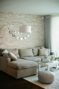 Grey living room with exposed brick wall. Brit.Co