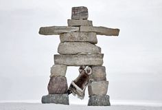 Inukshuk Landmark, Nanavut  Photograph by Michelle Valberg  This was our Inuk guide, Simon, hanging out on an inukshuk in Igloolik, Nunavut.