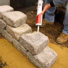Some retaining-wall blocks have locking mechanisms that allow them to be built to about 4 feet tall without extra engineering. Because we used tumbled blocks with no locking mechanisms, we used a construction adhesive on alternate courses. Remember, with locking blocks, you can remove blocks and start over if you make a mistake. But adhesive permanently bonds blocks, so work carefully./
