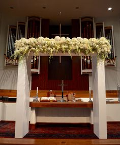 White modern wedding floral arch. Clean and stoic. Mounded white and ivory florals along the top. #hollidayflowers #memphisweddings