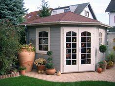 Dieses 5-Eck-Gartenhaus erstrahlt im maritimen Look: Große Terrakotta-Gefäße schmücken die Terrasse rund um das hellgraue Gartenhaus.