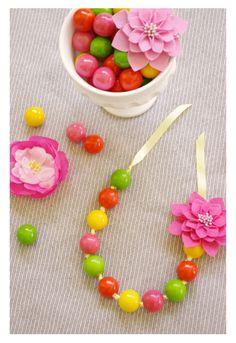 Kauwgomballenketting Dit is wat je nodig hebt: 1. Kleurrijke kauwgomballen 2. Lint 3. Metalen spiesen 4. Versieringen zoals bloemen en/of linten Neem eerst een metalen spies en maak gaatjes in de kauwgomballen. Rol het uiteinde van je lint samen duw het lint vervolgens door het gaatje van de kauwgombal. Gaat het moeizaam, gebruik de metalen spies om het lint door de kauwgombal te duw. Rijg zoveel gekleurde kauwgomballen aan het lint tot je denkt dat dit voldoende is. Je kunt tu