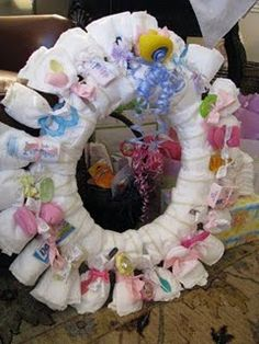 Diaper Wreath... I know, whoa! Using a wreath form from Michael's she wrapped it with diapers and tied each with a rubber band first then she hid the rubber bands by attaching toys, baby spoons, teethers, socks, a paci, travel-sized toiletries and hair bows with ribbon.