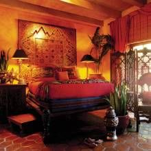 In the master, a new ceiling panel decorates the wall behind the bed. Other furnishings here include a moucharaby screen, floor lamp with goatskin shade, sub-Saharan African chair, and Moroccan pottery. Southwest influences include Saltillo tile floors and the Mexican star on the bedside table.
