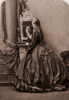 1858:  A Victorian woman in a crinoline with her hair in long plaits which reach to her waist, is looking at herself in a mirror. Photo: Oscar Gustav Rejlander, Getty Images / Hulton Archive