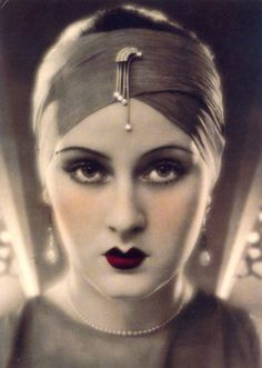 1930's french model: deep red-plum lips with sharp penciled line along with pale skin and smudged liner. A perfect look to use for the modern lady.