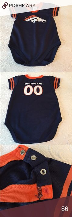 Denver Broncos onesie 12 months Super adorable jersey fabric Broncos onesie. One of the buttons on the shoulder needs to be glued to the fabric (which it was like this when I bought it). Can be worn without fixing button as that's how my son wore it. Excellent condition otherwise. Great onesie for your little Broncos fan!! Smoke free home. NFL Team Apparel One Pieces Bodysuits