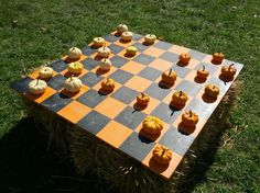 So cute for fall! Giant checkerboard set on a bail of hay with tiny pumpkins as game pieces.
