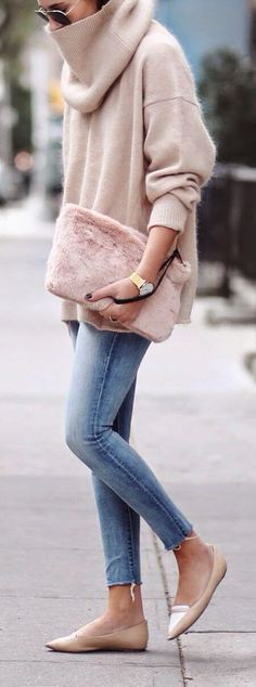Classy woman in a beige oversized sweater and blue skinny jeans
