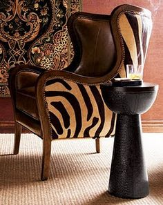 Terra cotta colored walls, intricate tapestry, zebra fur and leather chair, and hammered metal table that resembles a djembe drum.