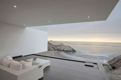 Casa VU is a minimalist house located in Lima, Peru, designed by TDC. The project is set on a cliff with a steep slope and a privileged view to an isle on the sea. Every room tends to open up to this natural surrounding through overlapped volumetries which generate shadows and open spaces such as the terrace which ends up becoming a contemplation space. At this house, architecture and structure merged in order to create two white volumes (un-gravitational) set over two earthly volumes (mas