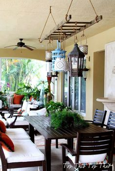 Create a warm, eclectic look on a porch or patio by using a ladder as frame to hang lanterns of various shapes, colors, and heights. Get the tutorial at Top This Top That.   - CountryLiving.com