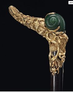 A Continental ormolu-mounted nephrite cane made with a handle with a fully sculpted snail amongst naturalistically modeled lush vinery and flowers, late 19th Century, (estimate: $5,000 – 8,000) Handmade Walking Sticks, Walking Sticks And Canes, Wooden Walking Canes, Wooden Canes, Cannes, Famous Jewelers, Cane Handles, Cane Stick, Sculpting