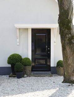 Boxwood planters curb asymetric appeal black front door ; Gardenista
