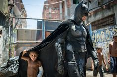Children play around a man disguised as Batman at the Favela do Metro slum, area just near the Maracana stadium, in Rio de Janeiro, Brazil, on January 9, 2014. Families living in this shantytown within a stone's throw of Rio's mythical Maracana stadium refuse to have their homes demolished as part of a project to renovate the district before the FIFA World Cup circus pitches camp in June. AFP PHOTO / YASUYOSHI CHIBA/AFP/Getty Images.  More Photography here.