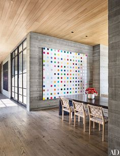 A Damien Hirst painting presides over the dining room, where Alvar Aalto chairs by Artek surround a bespoke table | archdigest.com