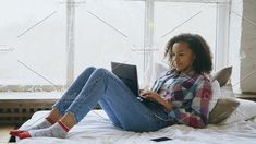 Happy mixed race girl having video chat with friends using laptop camera while lying on bed
