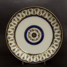 A Large 18th Century Sevres Hard-Paste Porcelain Dish 1792. Decorated with Garden Flowers, Blue and Gilding. The Base with Interlaced L`s for the Sevres Porcelain Factory, `OO` for 1792 and `DT` for Nicholas Dutenda (worked at Sevres 1765-1802). A pair of Sevres Porcelain sauceboats from this service of 1792 can be found at the Victoria and Albert Museum in London see : Sevres Porcelain, Vincennes and Sevres 1740 1800 (Erikson and De Bellaigue, Faber and Faber, 1987) page 353 plate 158.
