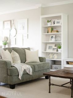 Summer is all about hues that make you feel more relaxed. In a room that's mostly white with wooden touches, a subtle green couch stands out just enough.  See more at A Burst of Beautiful.