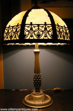 """This beautiful electric table lamp is a fine example of a Rainaud / Miller slag glass lamp from the early 20th century. There are eight curved, caramel slag glass panels mounted in a finely detailed metal frame. The delicate pattern of metal lacework is complimented by the detail in the solid parts of the frame and in the stand. The frame and stand are painted with an """"old gold"""" finish."""