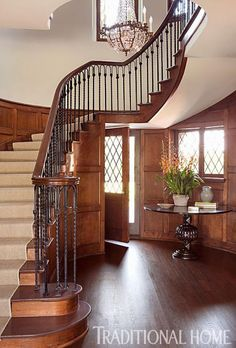 Dark stain, white painted walls, and a curving staircase make a grand entry. - Traditional Home ® / Photo: Karyn Millet / Design: Joe Lucas and Parrish Chilcoat