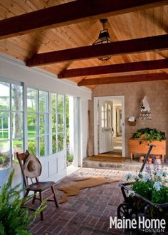 Breezeway with white walls, brick floors and multiple windows. Wood ceiling beams. Rabbit shaped rug. No longer listed on the site