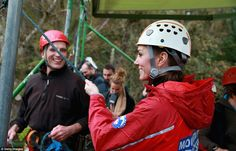 The Duchess of Cambridge holds Prince William's support rope as he abseils down the wall...