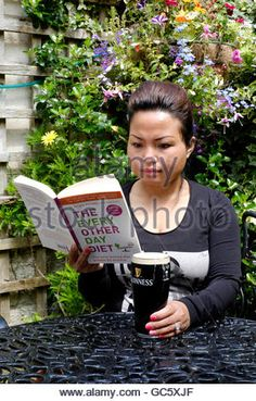 young female reading dieting book while drinking beer in a pub garden in england uk - Stock Photo