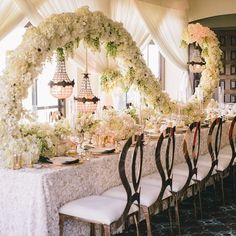 revelryeventdesign#Featured on @InsideWeddings New Website! 1920's Vintage Seaside Romance #LuxeLaunch2015 | Our Infinity Rose Gold Chairs echo the curves and arch in this exquisite floral design.