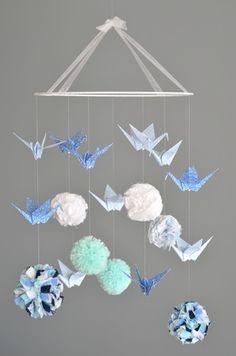 Mobile pompons (tissu, laine, liberty...) et grues en origami Modèle déposé. Matériaux utilisés : - Coton blanc, bleu marine, bleu ciel, bleu clair et vert d'eau - 14212413