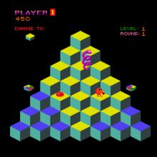 Q*Bert old school video game.  A square video game screenshot that is a digital representation of a multicolored pyramid of cubes in front of a black background. An orange spherical character, a red ball, and a purple coiled snake are on the cubes. Multicolored discs are adjacent to the left and right sides of the pyramid. Above the pyramid are statistics related to gameplay.