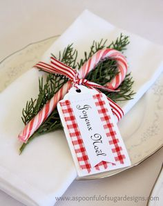 White cotton napkins, sprig of greenery, a candy cane, red & white striped ribbon and a pretty tag... table setting ideas for Christmas