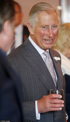 Prince Charles enjoys a joke and a tipple of what appears to be whisky inside The Clutha Bar in Glasgow