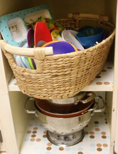 Store kids bowls and plates in a basket. They are often odd sizes and don't store well on shelves. Put them in a lower cabinet so kids can reach them and set the table.