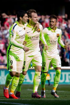 Ivan Rakitic (2L) of FC Barcelona celebrates scoring their opening goal with team mates Luis Suarez (L) and Neymar JR. (R) during the La Liga match between Granada CF and FC Barcelona at Nuevo Estadio de los Carmenes on February 28, 2015 in Granada, Spain.