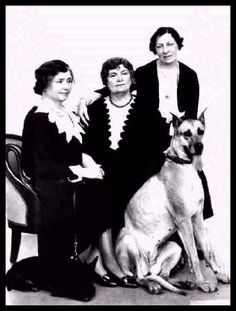 studio portrait (from left to right) of Helen Keller, Anne Sullivan, and Polly Thomson, seated on a divan. Helen Keller's Great Dane and Anne Sullivan's Scottish Terrier are seated at the women's feet. Circa 1932.