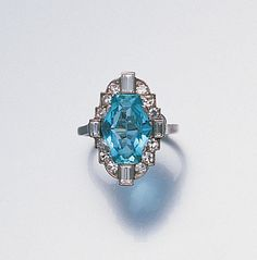 An art deco aquamarine and diamond dress ring, circa 1925  The elongated hexagonal mixed-cut aquamarine to a four-claw setting, within a border of single-cut diamonds with four collet mounted baguette-cut diamond highlights