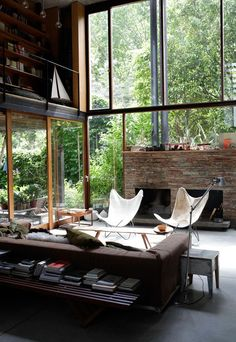 fireplace surrounded by windows | space: a living room surrounded by greenery