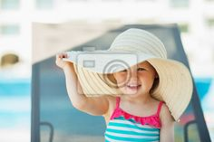 Stock photo of Baby in beach hat sitting on sun bed 43257583 - image 43257583