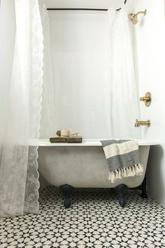 Instead of opting for a pricier custom tub, Jenna Sue purchased a basic white porcelain and cast iron claw foot tub to replace the bathroom's golden yellow fibreglass tub-shower combo. She then painted it a warm gray color to achieve the look she was aiming for, and added special lime paint and lime wax for some DIY patina. She also spray painted the claw feet black to save some more cash.